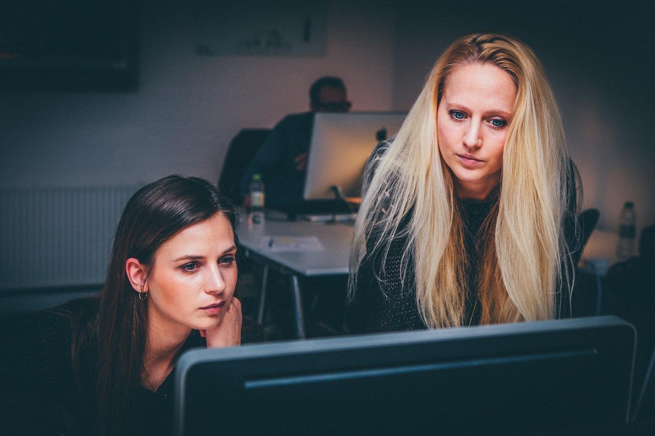 women looking over laptop